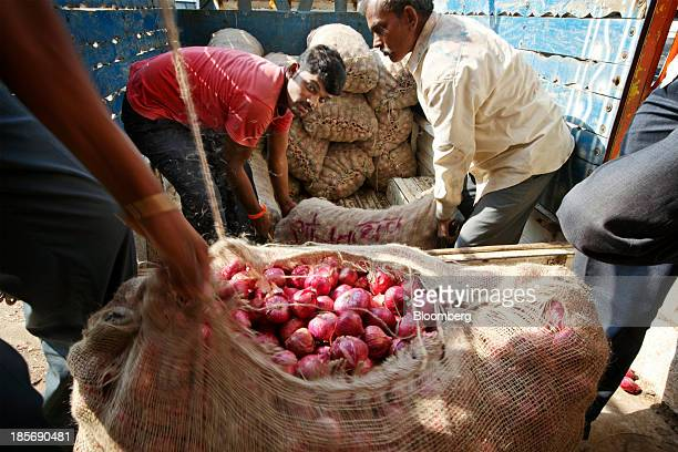 Workers deliver bags of onions to a wholesale market in Nashik Maharashtra India on Wednesday Oct 23 2013 Onion prices in India may extend a record...