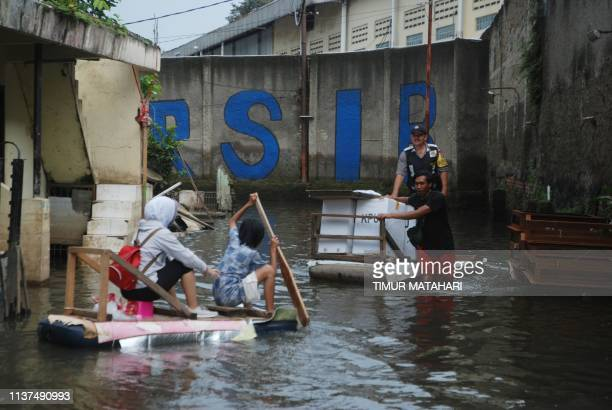 Workers deliver ballot boxes by makeshift raft to flooded areas in Bandung on April 16 on the eve of the country's general elections From sending...
