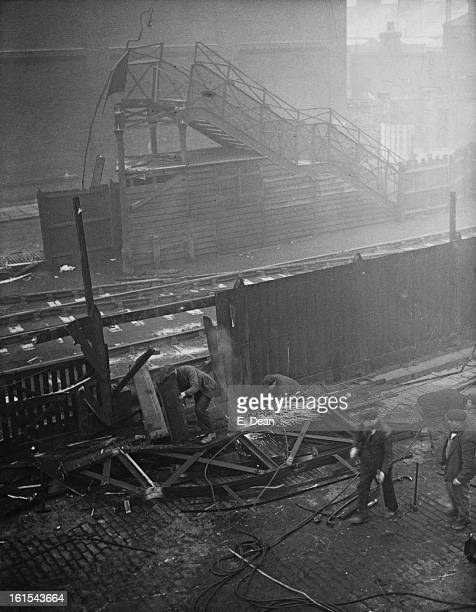Workers demolish the remains of a footbridge spanning the railway line from North Woolwich Road to Factory Road in Silvertown London after it...