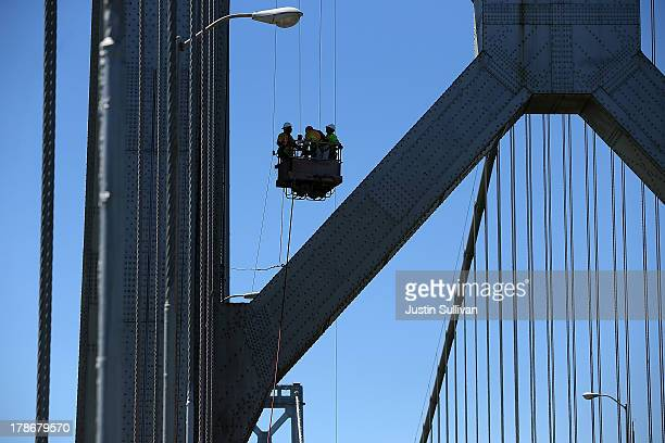 Workers descend from a tower of the western span of the San Francisco Oakland Bay Bridge as they perform maintenance before the opening of the new...