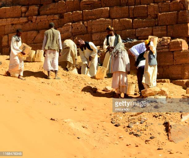 workers dig at the meroe pyramids - nubian tombs in the sahara desert - unesco world heritage site, begarawiyah, sudan - east stock photos and pictures