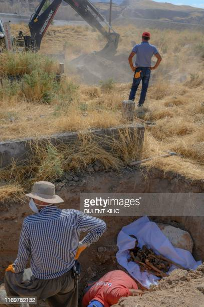 Workers dig up a corpse that will be transferred from the old cemetery to the new Hasankeyf cemetery on September 13 in Hasankeyf on the banks of the...