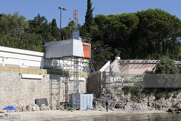 Workers disassemble an elevator on the public beach near the Saudi King's villa in the GolfeJuan seaside resort in Vallauris southeastern France on...