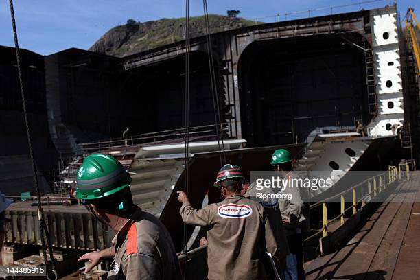 Workers discuss moving a heavy part of a Petroleo Brasileiro SA oil tanker under construction at the Maua SA shipyard in Niteroi Brazil on Thursday...