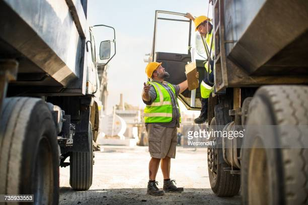 Workers discussing at quarry, standing between trucks
