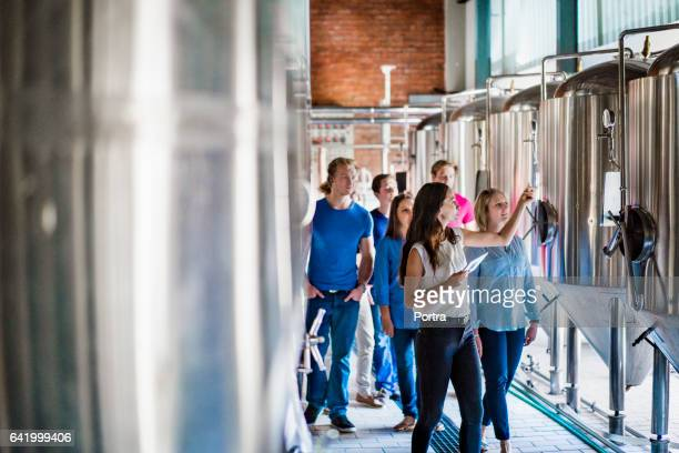 Workers discussing over vats in brewery