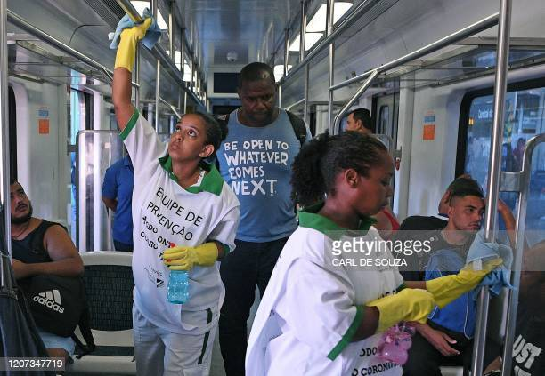 Workers disinfect handrails on a train as a precautionary measure against the spread of the new coronavirus, COVID-19, at Rio de Janeiro's Central...