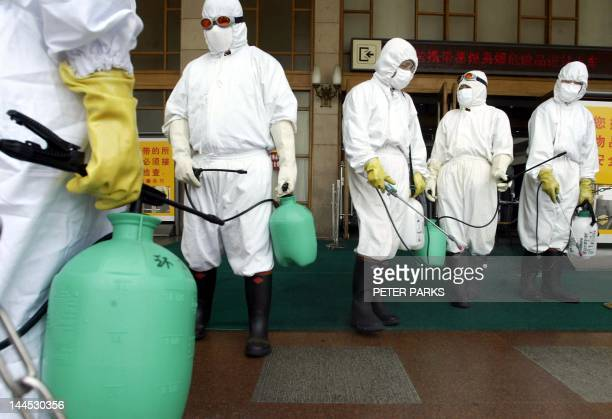 "Workers disinfect the outside of Beijing railway station in the fight against SARS, 25 May 2003. Beijing has seen a ""notable downward"" trend in the..."
