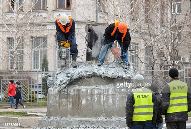 Workers dismantle a flagpole after its was damaged by a blast early on April 7 2015 in Kharkiv Two bomb attacks early Tuesday shook Ukraine's second...