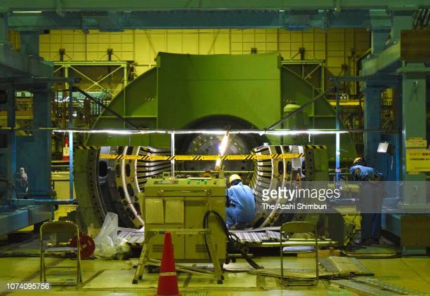 Workers dismantle a power generator as a part of decommissioning work of No2 reactor at the Chubu Electric Power Co's Hamaoka Nuclear Power Plant on...