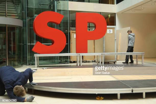 Workers dismantle giant letters of the logo of the German Social Democrats following the presentation of the SPD members of the next German...