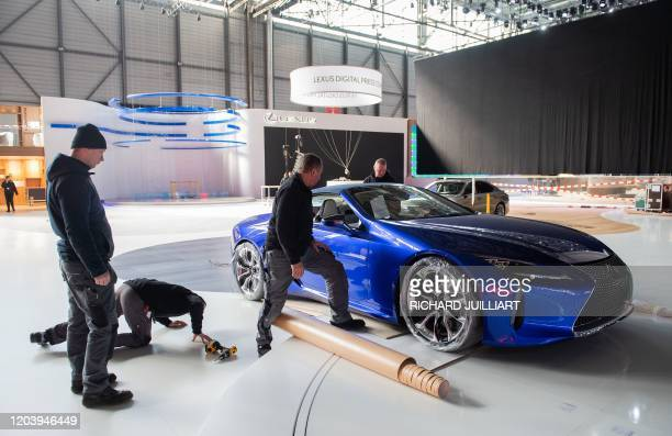 Workers dismantle on February 28, 2020 at the Geneva International Motor Show, which has been cancelled due to the Covid-19 epidemic. - The Geneva...