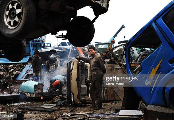 Workers dismantle scrapped cars at an auto scrapyard on April 21 2009 in Wuhan of Hubei Province China Official statistics showed that China's auto...