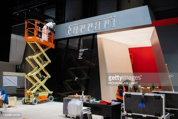 Workers dismantle the Ferrari stand on February 28, 2020 at the Geneva International Motor Show which has been cancelled due to the Covid-19...
