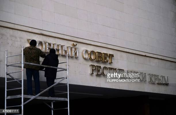 Workers dismantle the inscription written in the Ukranian language reading 'The Supreme Council of the Autonomous Republic of Crimea' on the Crimean...