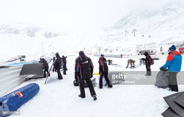 Workers dismantle the venue after the cancellation of the Men's Giant Slalom race at the FIS Alpine Ski World Cup in Soelden Austria on October 29...