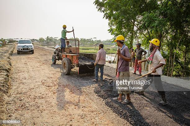 Workers distribute asphalt at a road construction site on April 11 2016 in Khulna Bangladesh