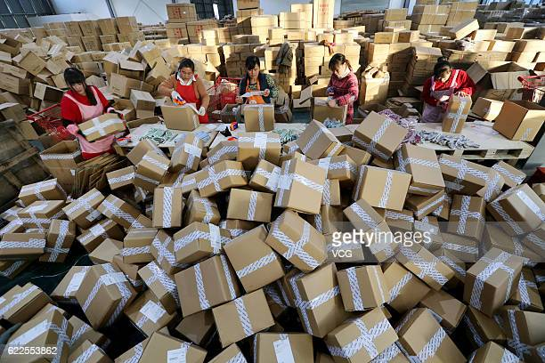 Workers distribute express parcels at a logistics centre of China Post during Alibaba Group's Singles' Day global shopping festival on November 11,...