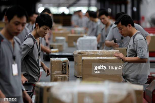 Workers distribute packs at SF Express on November 11 2013 in Shenzhen China Singles' Day has become China's Cyber Monday The sales volume on...