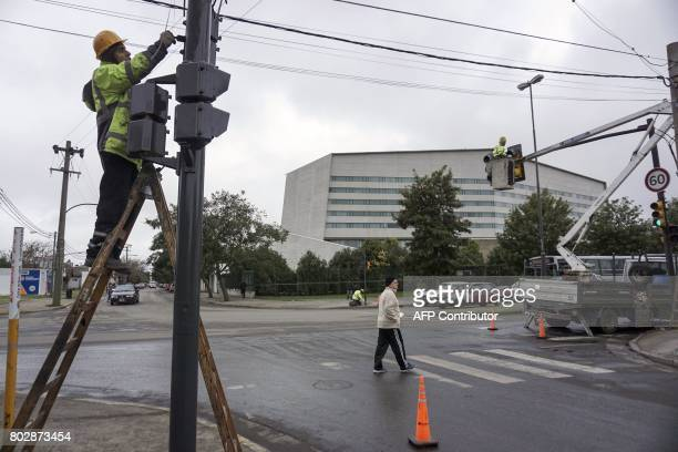 Workers do maintenance to traffic lights in front of the venue where Barcelona's football star Lionel Messi of Argentina and Antonella Roccuzzo will...