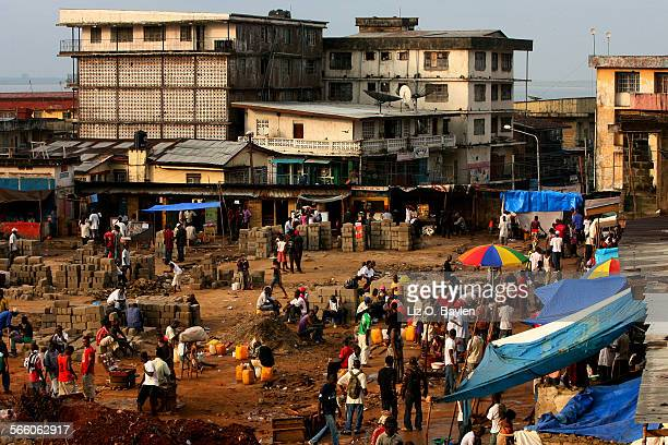 Workers do new construction on a market in Freetown Many citizens watch surprised that a campaign promise to build up the city wasn't idle