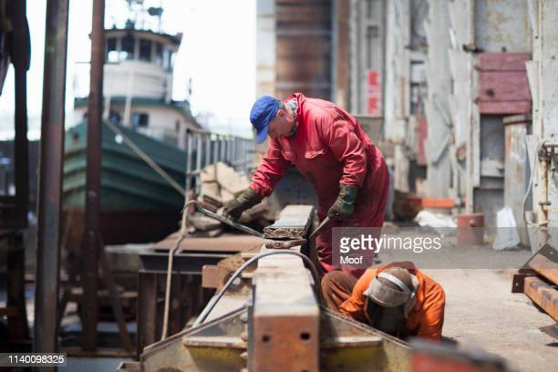 workers doing maintenance in shipyard workshop - nautical vessel stock pictures, royalty-free photos & images