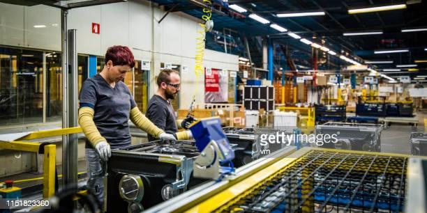 arbeiter, die qualitätskontrolle an waschmaschinen durchführen - fließbandfertigung stock-fotos und bilder