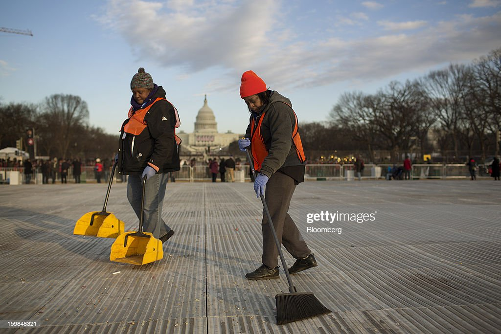 Workers Donna Laws, right, and her cousin Melinda Laws sweep up at the National Mall during the U.S. presidential inauguration in Washington, D.C., U.S., on Monday, Jan. 21, 2013. A crowd estimated by police to be as large as 700,000, including warmly dressed women with American flags stuck in their hair, a smattering of celebrities and many Republicans, gathered today to witness President Barack Obama take his second oath of office on the steps of the U.S. Capitol. Photographer: Victor J. Blue/Bloomberg via Getty Images