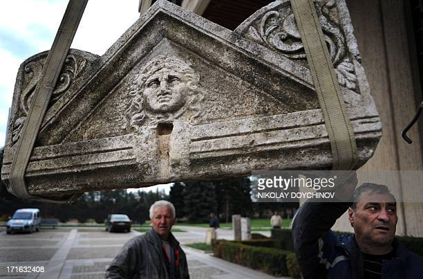 Workers download a part of a Roman sarcophagus dated back to the 2th century AC in National museum of history in Sofia on April 8 2011 Exquisite...
