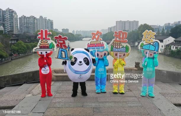 Workers dressed as Beijing 2022 Olympic and Paralympic Winter Games mascots Bing Dwen Dwen and Shuey Rhon Rhon , and Hangzhou 2022 Asian Games...