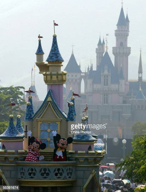 Workers dressed as Disney cartoon figures Mickey and Minnie wave to tourists at the Hong Kong Disneyland on September 12 2005 in Hong Kong China...