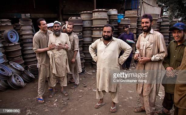 Workers dressed in salwar kameez, a Muslim clothing, in flip flop, thong, recycle car parts