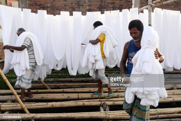 Workers dry fabric under the sun before dyeing them at a factory in Narayanganj. Most of the time workers dyeing clothes without wearing gloves and...
