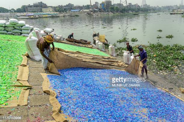 Workers dry recycled plastic chips on the banks of Buriganga River in Dhaka on September 22 2019