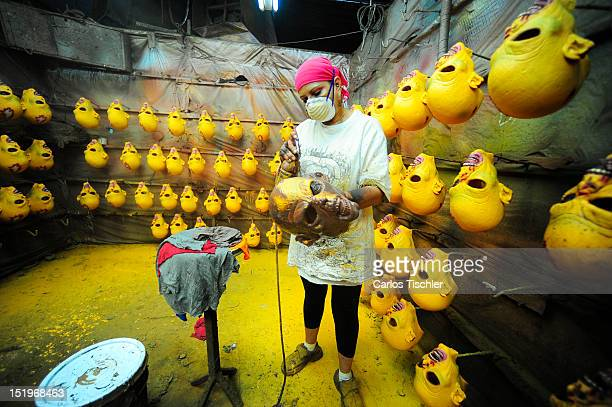 Workers during the manufacture of latex masks for Halloween parties on September 10, 2012 in Cuernavaca, Mexico.