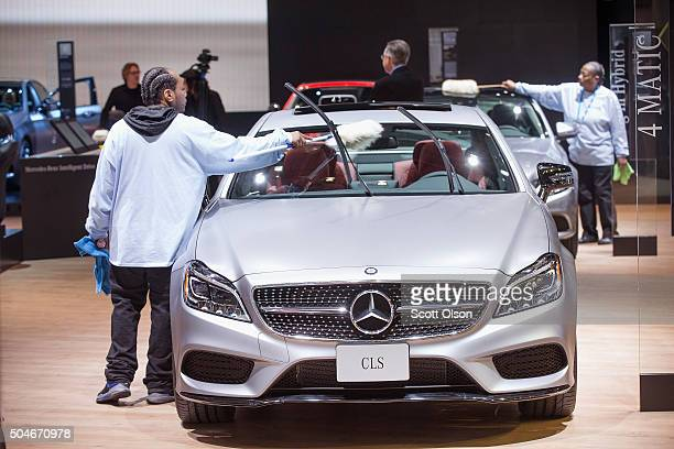 Workers dust of Mercedes cars on display at the North American International Auto Show on January 12 2016 in Detroit Michigan The show is open to the...