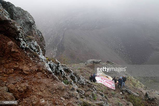 Workers employed by a cooperative working for the Vesuvius park hold a banner during a protest in the crater of the volcano on April 23, 2012 near...