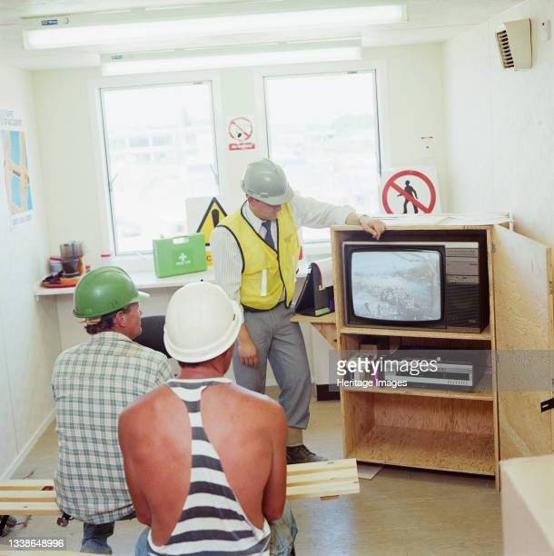 Workers employed on the Glaxo Research Centre construction site in Stevenage watching a safety training video. This image is part of a batch with...