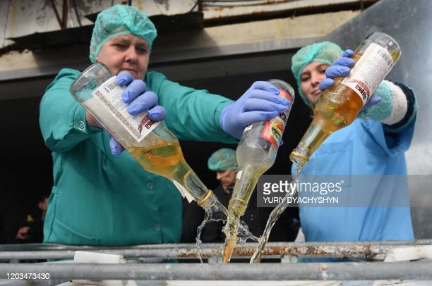 Workers empty bottles of adulterated vodka to be destroyed in the town of Vynnyky, western Ukrainian Lviv region, on February 26, 2020. - Ukrainian...