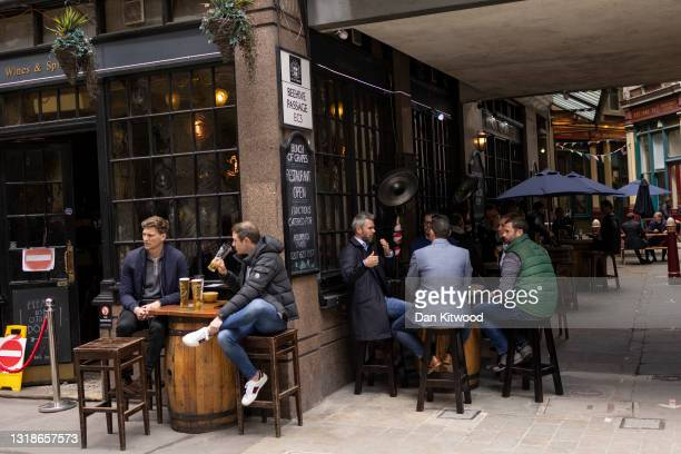 Workers enjoy drinks in a pub near Leadenhall Market in the square mile on May 18, 2021 in London, England. Workers have begun to return to the City...