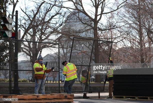 Workers erect a fence around the U.S. Capitol Building the day after a pro-Trump mob broke into the building on January 07, 2021 in Washington, DC....