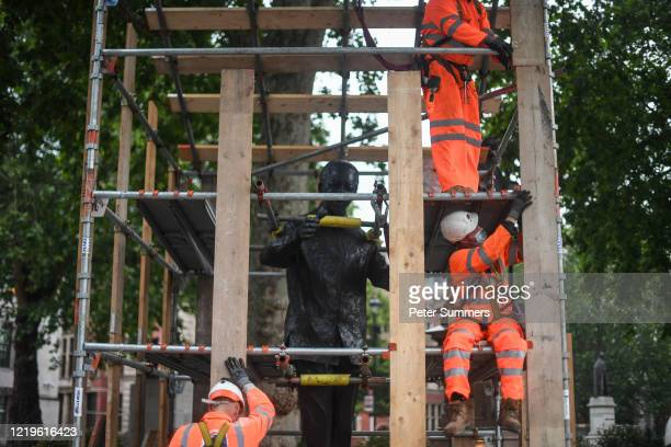 Workers erect a protective barrier around the statue of Nelson Mandela in Parliament Square in anticipation of protests taking place in the city...
