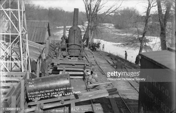 Workers erect a steam driven pile driver while others survey for the railroad extension from the village of Prairie du Sac to the dam site on the...