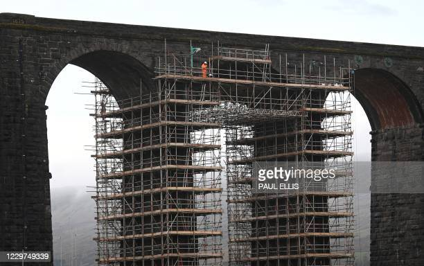 Workers erect scaffolding ahead of planned restoration work on the Ribblehead Viaduct, near Settle, northwest England on November 23, 2020. -...