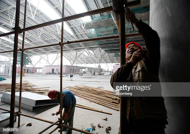 Workers erect scaffolding at the nearly completed new terminal of the Shanghai Pudong International Airport expansion project in Shanghai China on...