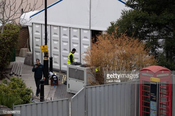 Workers erect shelving units and install refrigeration systems inside what is believed to be a temporary mortuary built to handle a possible spike in...