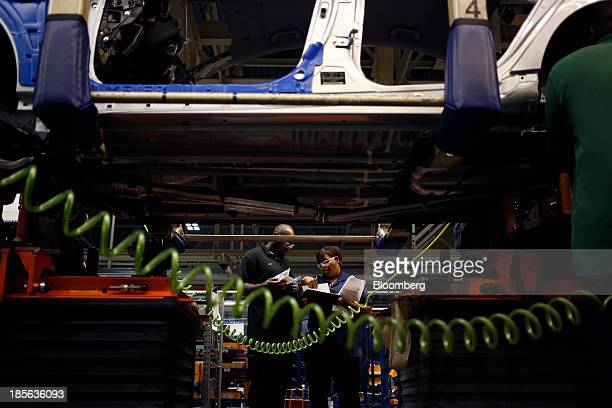 Workers examine paperwork during production of Sonata and Elantra vehicles at the Hyundai Motor Manufacturing Alabama assembly plant in Montgomery,...