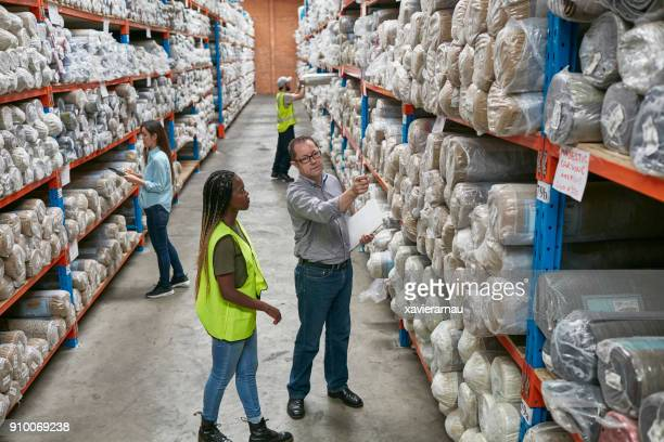 Workers examining carpets on shelves in factory
