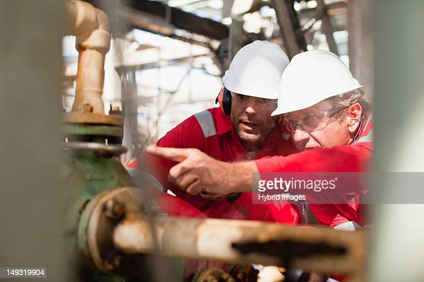 workers examining equipment on site - air valve stock photos and pictures