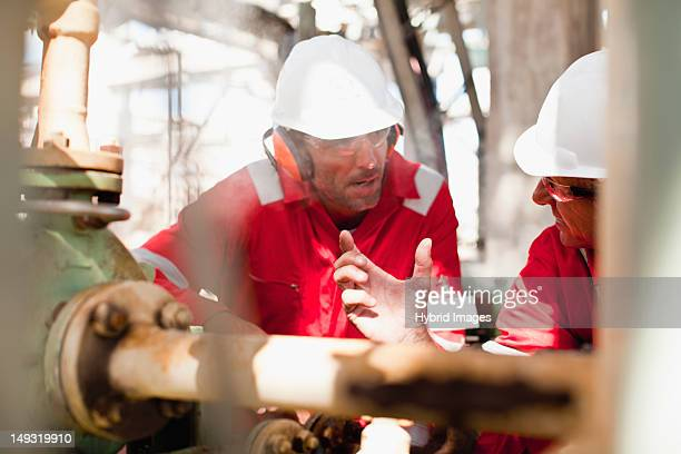 Workers examining equipment on site